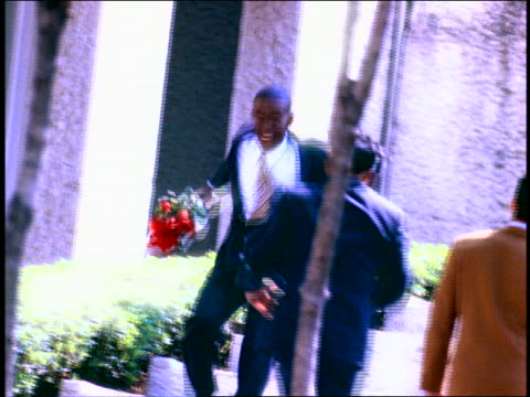 vídeos de stock, filmes e b-roll de slow motion excited black man in suit carrying bouquet of roses kicking up heels / mexico - superexposto
