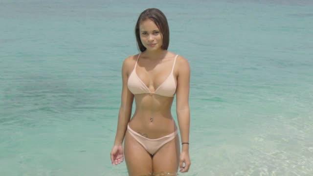 vídeos de stock e filmes b-roll de slow motion: exotic woman in bikini looks at camera while in clear water - câmara fotográfica