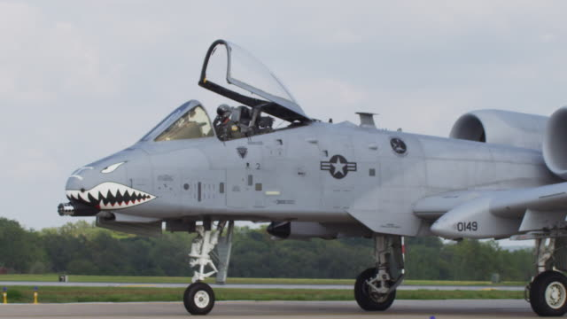 Slow motion extreme close up A-10 Warthog US military jet moving down the runway with the cockpit open.