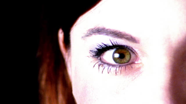 high contrast overexposed slow motion extreme close up brown eye of young woman looking to camera then away in studio - overexposed video stock e b–roll