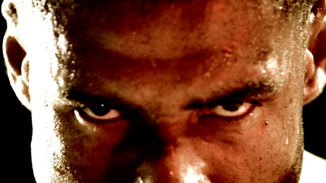 Slow motion extreme close up face of Black boxer sweating and looking down