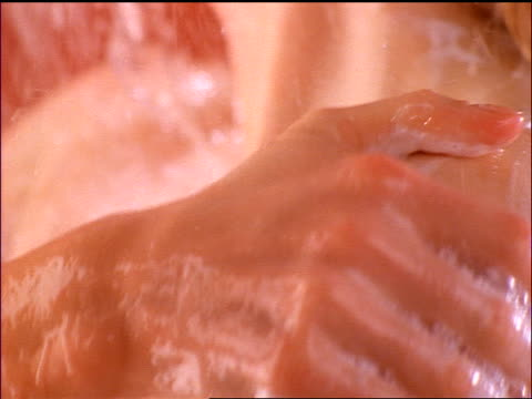 slow motion extreme close up hand of woman washing shoulders with soap in shower