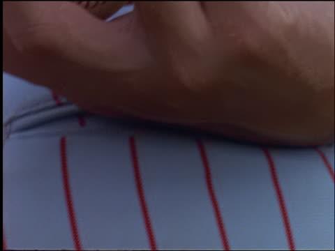 slow motion extreme close up pitcher's holding baseball behind his back - 野球ボール点の映像素材/bロール