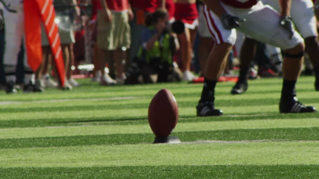 slow motion extreme closeup of a football on a tee at the start of a collegiate game; kicker kicks the ball! - kicking stock videos & royalty-free footage