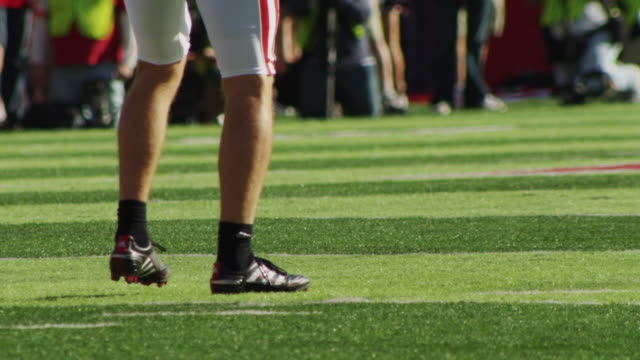 Slow motion extreme closeup of football as a collegiate football player punts the ball.