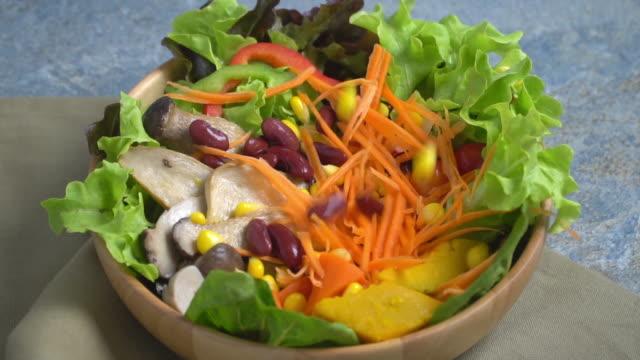 vidéos et rushes de ralenti la chute des légumes sur un bol de salade. - assiette