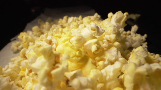 スローモーション落ちるポップコーンクローズアップマクロワイドアングルヒープ、カウンタートップに新鮮なバター脂っこい黄色のポップコーン - 塩味スナック点の映像素材/bロール