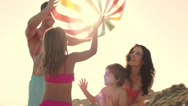 Slow motion family playing with beach ball on beach.