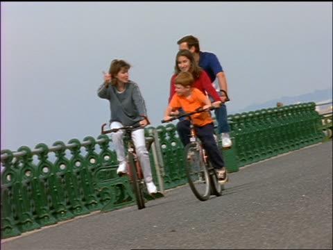 slow motion family riding bicycles on boardwalk / brighton, england - brighton england stock videos & royalty-free footage