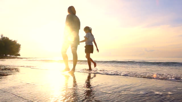 vídeos de stock e filmes b-roll de hd slow motion: family walk on a tropical beach at sunset - silhueta