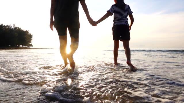 hd スローモーション: 家族が夕日で熱帯のビーチを歩く - スーパースローモーション点の映像素材/bロール