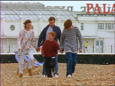 slow motion family walking on beach at Brighton in wind / Victorian Palace Pier in background / England