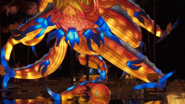 slow motion: fantastical flying fish sculpture lit up like lantern at night - multicolore video stock e b–roll