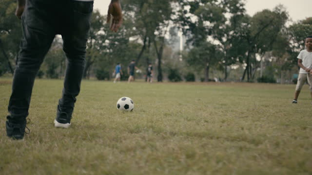 slow motion : father and son playing with soccer ball in park - young family stock videos & royalty-free footage