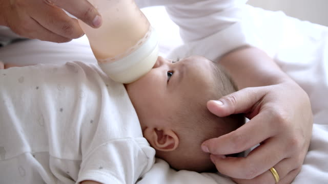 slow motion father is breastfeeding from a bottle. - baby milk stock videos & royalty-free footage