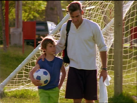 stockvideo's en b-roll-footage met slow motion father walking with arm around son holding soccer ball + talking to him - familie met één kind
