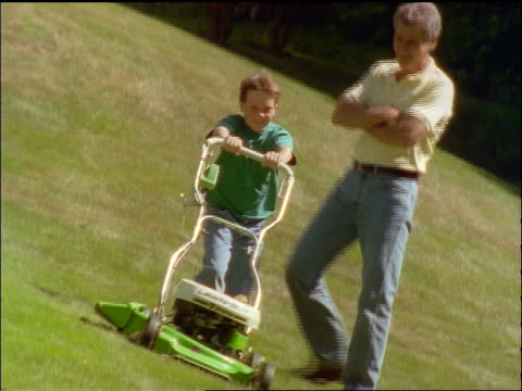canted slow motion father watching son mow lawn in backyard - housework stock videos and b-roll footage