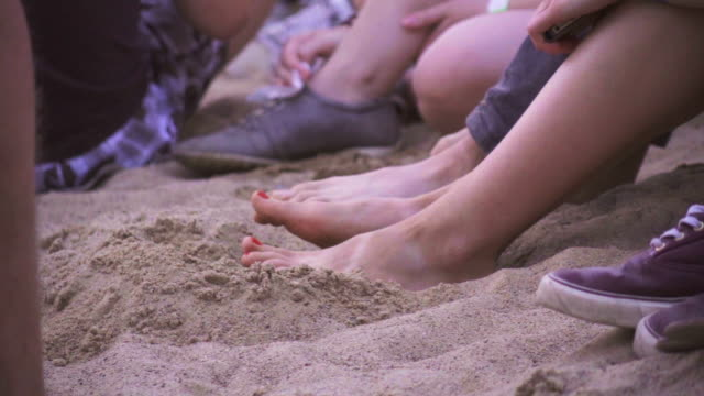 Slow motion feet on the beach keeping time
