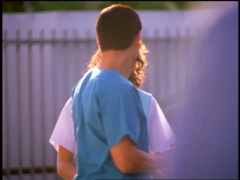 vidéos et rushes de slow motion female hospital volunteer + code blue nurse laughing + walking towards camera outdoors - parking