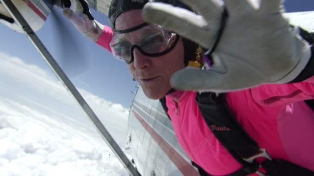 slow motion -  female senior skydiver exits airplane - only senior women stock videos & royalty-free footage
