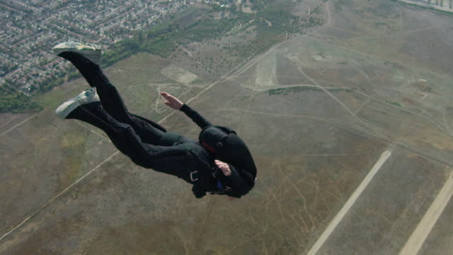 slow motion - female senior skydiver flies away - goggles sportswear stock videos and b-roll footage