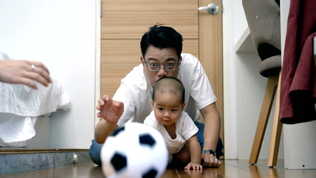 slow motion fhd clip footage of asian baby boy crawl and playing the ball on the wooden floor with father cheering up in the bedroom, family lifestyle concept - crawling stock videos & royalty-free footage