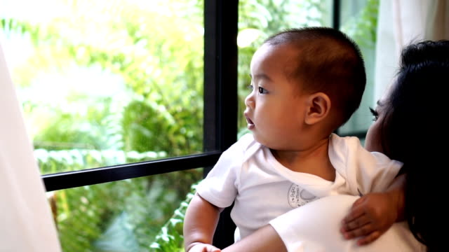 探していると、母親からモダンなロフトの家、家族および生活様式の概念を保持しているウィンドウ ガラスに触れることを見つめてアジア男の子のスローモーション fhd クリップ映像 - 見つめる点の映像素材/bロール