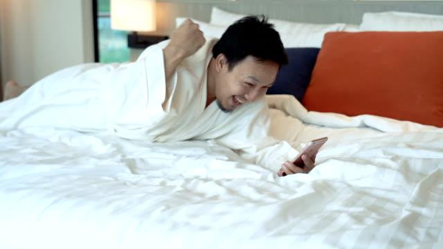 vidéos et rushes de slow motion fhd clip images d'homme asiatique jouer smartphone et surprenante en position couchée dans son lit le matin vers le concept d'hôtel de luxe chambre, style de vie et loisirs - expression positive