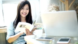 Slow motion FHD footage closeup of asian woman sitting and reading book in the morning with warm feeling at modern co-working space, Lifestyle and leisure concept