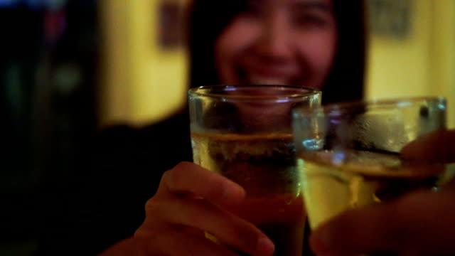 スローモーション fhd 映像を焼くことで友人とビールのガラスをチリンとアジア女性のクローズ アップ バーとレストラン、リラックス、概念を飲む - グラス点の映像素材/bロール
