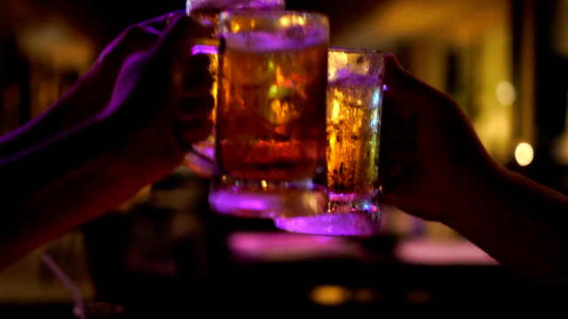slow motion fhd footage closeup of toasting and clinking glasses of beer, cheering together at bar and restaurant, relax and drink concept - pub stock videos & royalty-free footage