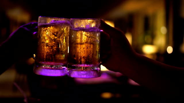 slow motion fhd footage closeup of toasting and clinking glasses of beer, cheering together at bar and restaurant, relax and drink concept - due persone video stock e b–roll