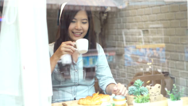 slow motion fhd footage of beautiful asian woman drinking coffee and enjoying the fresh croissant in the morning beside the window glasses at modern co-working space, lifestyle and leisure concept - croissant stock videos & royalty-free footage