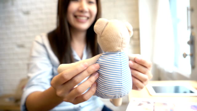 Slow motion FHD footage of beautiful asian woman playing bear doll with warm feeling at modern co-working space, Lifestyle and leisure concept