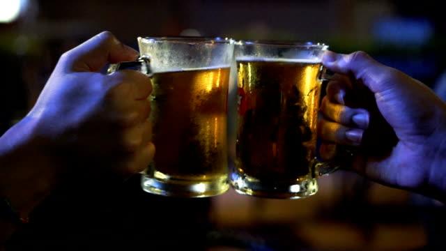 2 つのアジアのスローモーション fhd 映像男で一緒に応援して、ビールの乾杯と素晴らしく眼鏡バーとレストラン、リラックス、概念を飲む - ガラス点の映像素材/bロール