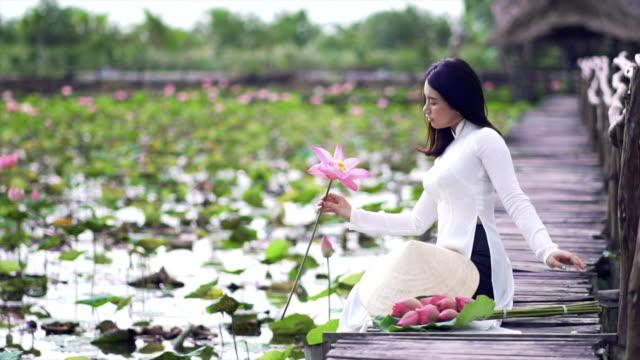 vídeos y material grabado en eventos de stock de movimiento lento de 4k tomas fhd retrato de hermosa mujer vietnamita sosteniendo el loto rosa y sonriendo en el puente de madera en concepto de viajes de lotus grande lago, vietnam, asia o asia sudoriental - posa del loto