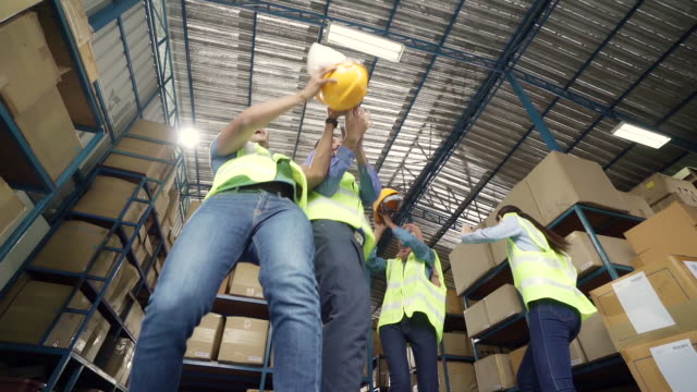 slow motion fhd : interracial team of warehouse worker and manager throw helmet in to the air to celebrate after finish working . using in business warehouse and celebration concept. - oregon coast stock videos & royalty-free footage