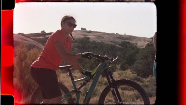 slow motion film footage of women gearing up for mountain biking trip in moab. - proiettore 8mm video stock e b–roll