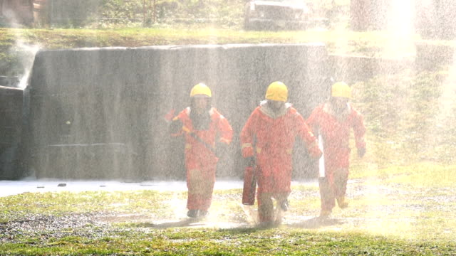 vídeos de stock e filmes b-roll de slow motion fire fighter running towards camera through the rain - bombeiro