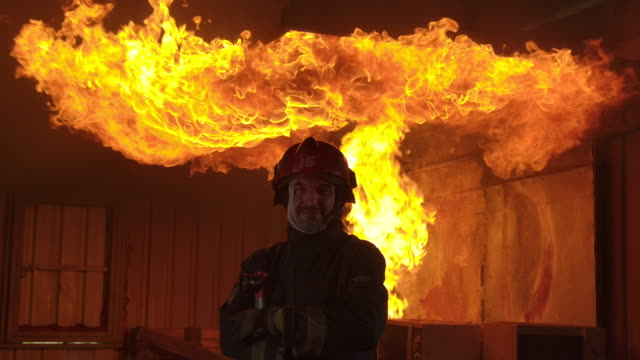 slow motion fire fighter standing towards the camera with fire in the background. - oxygen mask stock videos & royalty-free footage