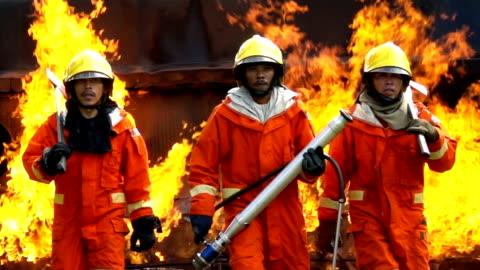 vídeos y material grabado en eventos de stock de slow motion fuego de combate caminando hacia la cámara con fuego en el fondo - casco herramientas profesionales