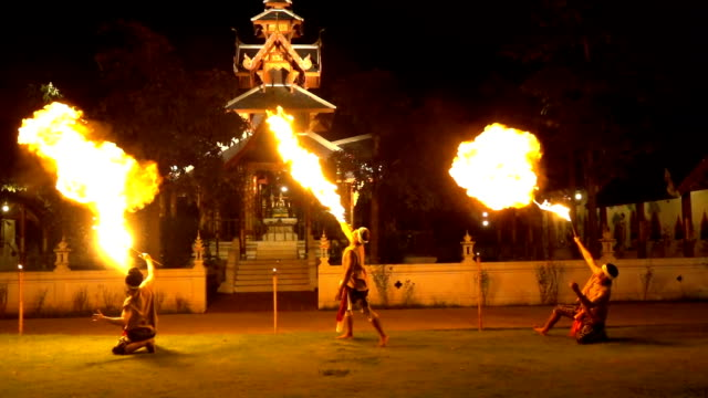 slow motion fire show: fire-eater men blowing flame from their mouth - lentezza video stock e b–roll