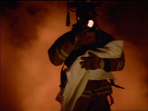 vidéos et rushes de slow motion firefighter in oxygen mask running out of smoke holding baby in his arms / stops + checks it - pompier
