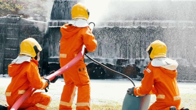 stockvideo's en b-roll-footage met slow motion: brandweerlieden bestrijding van een brand met schuim spray - schuimstof