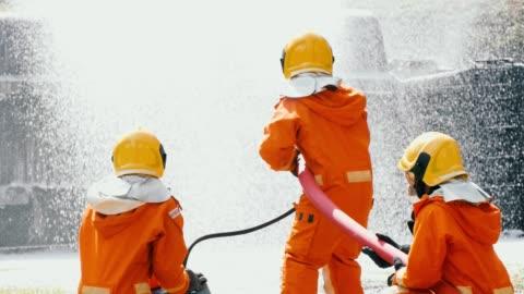 stockvideo's en b-roll-footage met slow motion: brandweerlieden bestrijding van een brand met schuim spray - reddingswerker