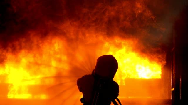 燃えている建物の中で火を消すために消防ホースを使用してスローモーション消防士