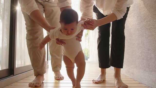 slow motion primi passi a piedi asia baby. - baby video stock e b–roll