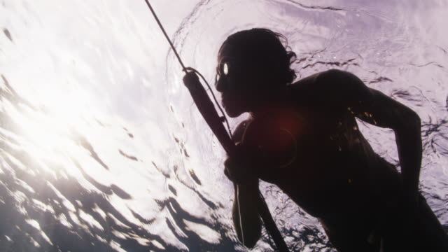 Slow motion, fisherman in Indonesia swims at surface