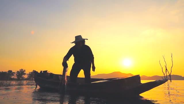 hd-slow-motion: fischer am boot angeln bei sonnenuntergang - fischereinetz stock-videos und b-roll-filmmaterial