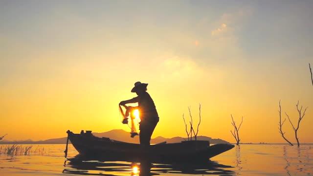 hd-slow-motion: fischer am boot angeln bei sonnenuntergang - fischen stock-videos und b-roll-filmmaterial